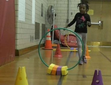 Young girl passing though obstacle course at family fun night