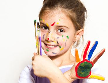Girl holding paint brushes