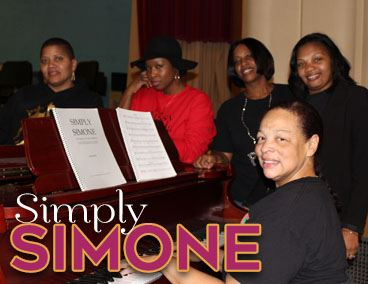 Image of cast around piano at play rehearsals